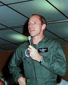 en mann i en jakke som holder en mikrofon i hånden.