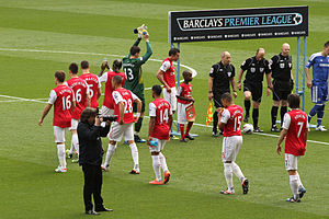 A coloured photograph of a group of men, dressed in red. They are walking in order to form a line. A man dressed in a green shirt places his hands together and raises them, in direction to his right. To the far right of the photograph, there is a man dressed in a blue kit, in line with three men who are dressed in black. Behind them is a placard with the words 'Barclays Premier League'.