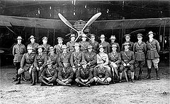 Twenty-five uniformed men standing or seated in front of a biplane with a four-bladed propeller