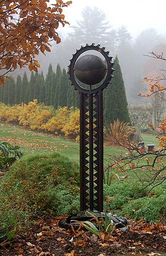 Bedrock Gardens - The sculpture 'Monocula' is in front of a row of Arborvitae.