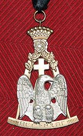 Photo en couleur d'un bijou maçonnique: on voit un aigle d'argent sur fond or surmonté d'une couronne et d'une croix