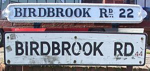 "Postcodes in the United Kingdom - Street name signs on Birdbrook Road, Great Barr, Birmingham, showing old ""Birmingham 22"" (top) and modern ""B44"" postcodes."