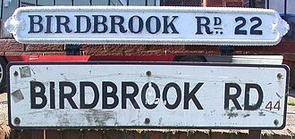 "B postcode area - Street name signs on Birdbrook Road, Great Barr, Birmingham, showing old ""Birmingham 22"" (top) and modern ""B44"" postcodes."