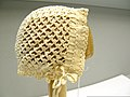 A bonnet, yellowed with age, displayed on a wooden form