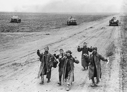 Five Soviet soldiers march to captivity on the Kerch Peninsula in May 1942. Three German tanks are visible on the background. Bundesarchiv B 145 Bild-F016237-0022A, Krim, russische Soldaten bei Gefangennahme.jpg