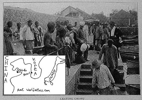 In this photo, several black men are standing around on the sidewalk of a concrete boat dock in China. The dock is in the center and left of the photo; the water is on the right side of the photo. A stairwell next to the water is inset in the dock. On the far side of the stairwell is the top of the stairs. Two black men, facing the viewer, are carrying suitcases down the stairs. The water is calm. Rowboats are tied along the concrete dock, from near to about six rowboats away. Then, the seawall makes a right turn. Beyond the water and the dock are wooden buildings at the top of the photo. They are one and two stories high. A map is sketched lower left which shows where Chi-fu is in relation to Seoul.