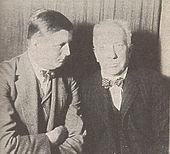 młody mężczyzna siedzący ze starszym, łysiejącym mężczyzną z wąsami