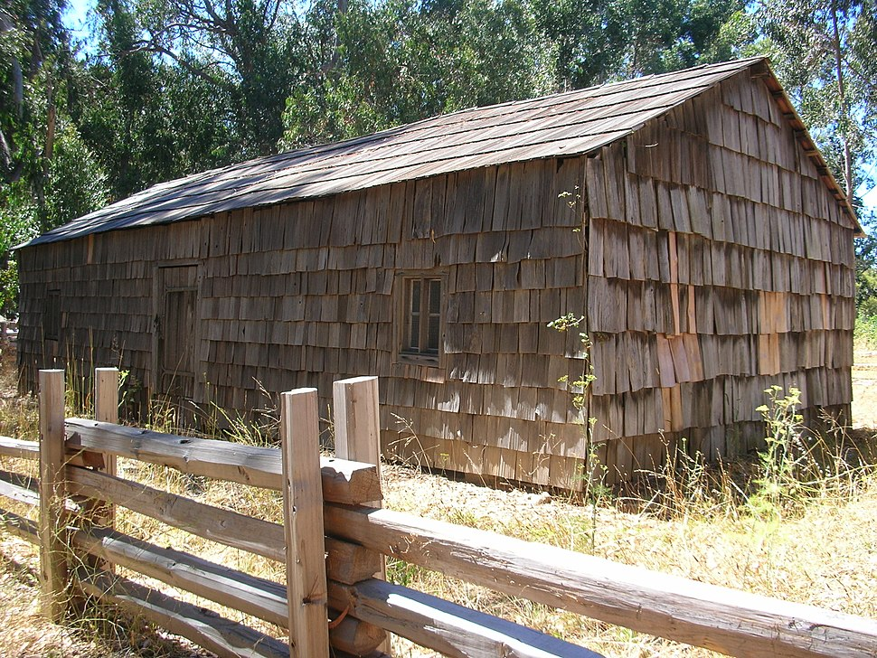 A shingled log cabin alongside a split rail fence is the oldest structure on the Big Sur coast.