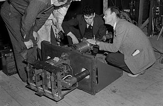 Calutron - Frank Oppenheimer (center right) and Robert Thornton (right) examine the 4-source emitter for the improved Alpha calutron.