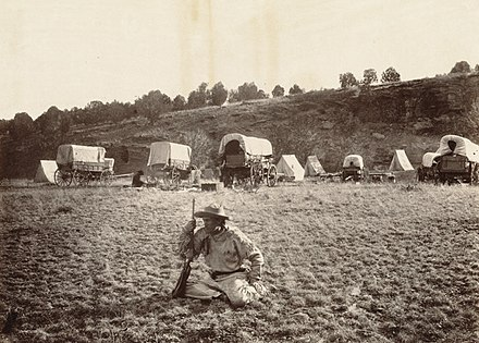 A railroad surveying party at Russel's Tank, Arizona in the 1860s Camp of surverying party at Russel's Tank, Arizona, on eastern slope of Laja Range, 1,271 miles from Missouri River. (Boston Public Library) (cropped).jpg