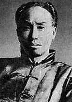 A man wearing dark clothes, starring straight at the camera