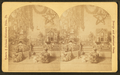 Christmas tree with toys around, including doll houses, by Roberts & Fellows.png
