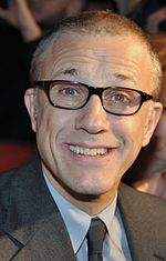 A middle aged man wearing glasses and a grey suit faces forward while smiling.