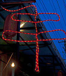 A red LED sign in the shape of two rectangles, one larger than the other, with a line through them, hanging from a building's eave against a darkening sky