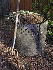 A pitchfork next to a compost bin