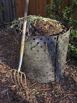 A pitchfork next to a compost bin.