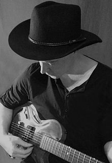 man playing guitar with hat on