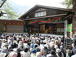 Outdoor stage with actors in traditional Japanese costumes.