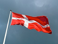 A Danish flag flies from a flagpole against the sky.