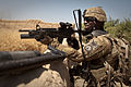 Defense.gov News Photo 110603-A-UJ825-032 - U.S. Army Sgt. 1st Class Andre Johnson uses a wall for cover as he stands guard near a wheat field in Malajat Kandahar province Afghanistan on.jpg