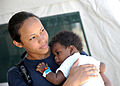 Defense.gov News Photo 110819-N-NY820-351 - U.S. Navy Hospitalman Cherie Williams holds a patient at the Terminal Varroux medical site in Port-au-Prince Haiti on Aug. 19 2011 during.jpg