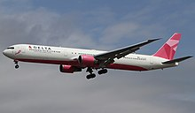 Twin-engine airliner with white and pink colors on approach with landing gear and flaps extended.