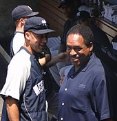 "A man in a navy blue and grey windbreaker with the word ""New"" visible stands on the left facing a man in a navy blue polo shirt who is looking up at the camera."