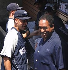 "A man in a navy blue and grey windbreaker with the word ""New"" visible stands on the left facing a man in a navy blue polo shirt who is looking away."