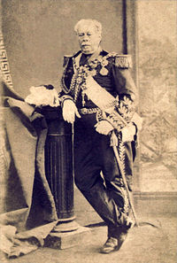 Full-length photographic portrait depicting an older man with moustache resting his right arm on a pedestal which holds a feathered bicorne hat, and wearing a heavily decorated military dress uniform with his left hand resting on the sword at his side