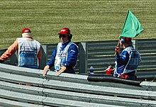 La bandiera verde segnala il termine del periodo in cui la safety car è sul circuito. La pista è sgombra e i piloti possono ripartire.
