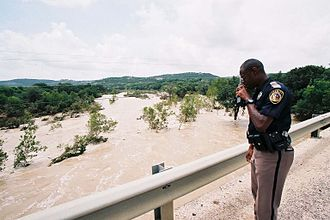 Cibolo Creek - A police deputy stands before a flooded Cibolo Creek in July 2002.