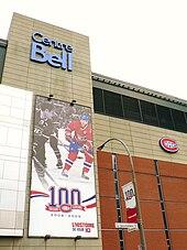 Фасад Белл Центр.  На стене вывешен баннер, посвященный столетию Канадиенс, на котором изображены два игрока: один черно-белый, а другой цветной, а логотип Canadiens стоит перед цифрой «100».
