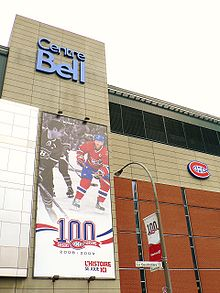 "Façade of the Bell Centre. On the wall is a banner celebrating the Canadiens centennial, featuring two players, one in black and white and one in colour, and the Canadiens logo in front of a ""100""."