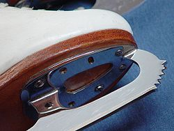 Close-up of a figure skating blade, showing the toe picks, hollow grind on the bottom surface of the blade, and screw attachment to the boot.