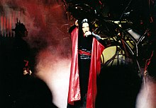 A brunette woman singing wearing a black and red kimono. Red lights and haze appear around her