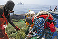 Gambian Navy Leading Seaman Sainey Ngum, right, checks the size of the holes of a fishing net on a vessel operating in Gambia's exclusive economic zone off the coast of West Africa June 20, 2012, to ensure it 120620-N-GN377-040.jpg