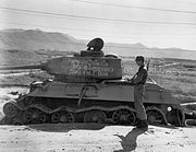 """Soldiers stand around a destroyed tank with writing on it reading """"Knocked out 20 July 1950 with the supervision of Maj. Gen. W.F. Dean"""""""