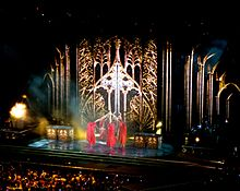 A huge stage showing a backdrop with gilded gates and people wearing red cloths pulling a rope above their head.
