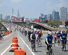 An elevated freeway in a city with bicyclists riding on it