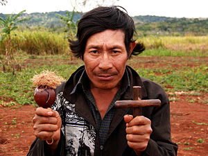 Indigenous peoples of South America - Guaraní holding maraca and cross, Paraguay, 2006
