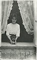Gwladys Ann Cartwright in the window of her house holding the family dog, Midge, Sep 1912.jpg