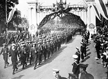 A group of men wearing military uniforms and carrying rifles marching under a decorated arch. The group is being led by a man carrying a sword. They are being watched by other men in uniform and a crowd of civilians.