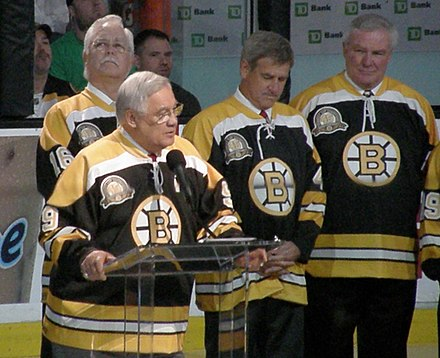 Orr (centre, background), stands next to Derek Sanderson, and John McKenzie while listening to Johnny Bucyk's speech. Orr has maintained relations with several former teammates from his career. Hail to the Chief (4457185531).jpg