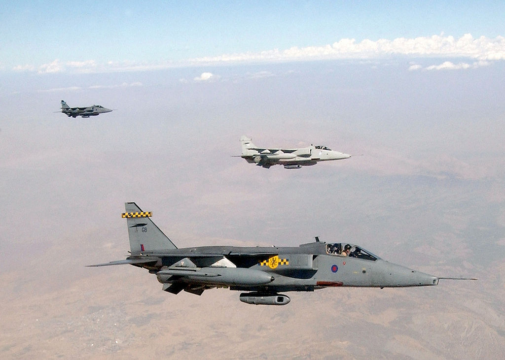 Grey jet aircraft flying above desert, with white aircraft further out, trailed be another jet.