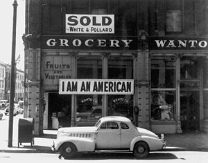 Anti-Japanese sentiment in the United States - A Japanese American unfurled this banner the day after the Pearl Harbor attack. The man was later detained nonetheless. This Dorothea Lange photograph was taken in March 1942, just prior to the Japanese American internment.