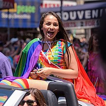 Jennings, dressed in LGBT pride wear, smiles to parade outlookers from a convertible car