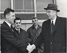 Diefenbaker, der einen Mantel über seinem Anzug trägt, schüttelt einem lächelnden Mann die Hand.  Im Hintergrund stehen zwei andere Männer, die weniger beeindruckt aussehen.