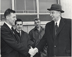 Diefenbaker, wearing a coat over his suit, shakes hands with a smiling man. Two other men, looking less impressed, are in the background.