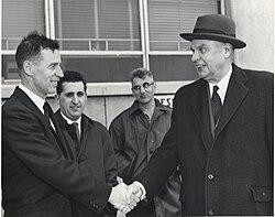 Diefenbaker, der einen Mantel über seinem Anzug trägt, gibt einem lächelnden Mann die Hand.  Zwei andere Männer, die weniger beeindruckt aussehen, sind im Hintergrund.