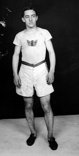 Johnny Hayes - Johnny Hayes, wearing the Winged Fist of the Irish American Athletic Club, posing for a studio portrait shortly after his 1908 Olympic Marathon victory.